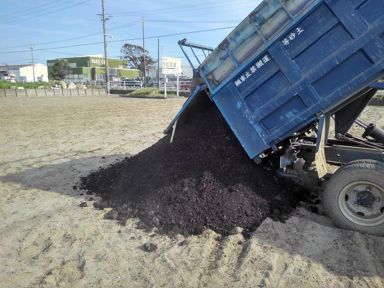 ダンプで運んだ堆肥を畑に降ろす作業